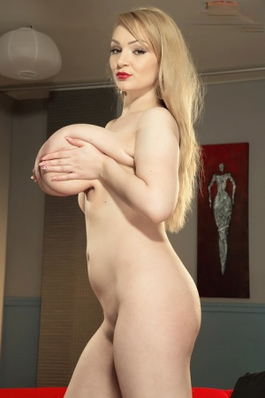 Blonde boob model Micky Bells hefts her giant juggs after getting undressed