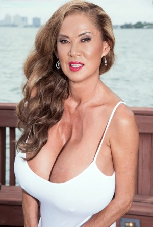 Asian woman Minka sets her giant tits free of a dress on a waterside patio