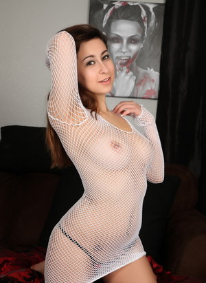 Brunette solo girl lifts up her see through mesh top in a thong