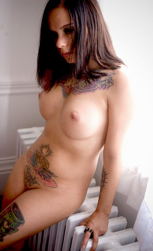 Chubby girl with tattoos Nyx holds a cross in hands while covering her pussy