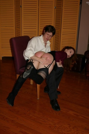 Redhead woman Summer Hart has her ass spanked over a man's knee in nylons