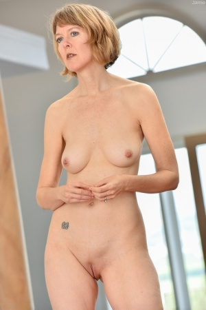 Older lady with short hair flaunts her small tits and shaved pussy in the nude