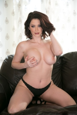 Busty housewife Emily Addison touches her goodies on the leather sofa