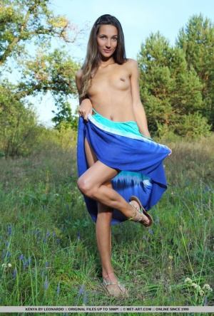 Blue eyed Kenya undressing outdoors to pose nude on her knees in the grass