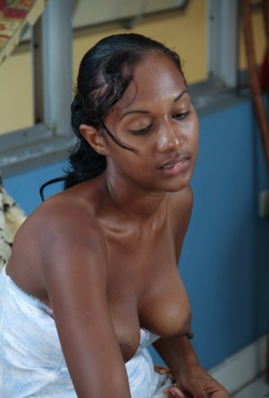 Young black girl teases her hairy pussy with a sucker after she gets naked