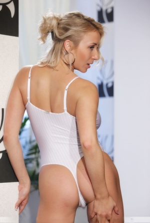 Young blonde Ella C unveils her great boobs as she peels off her white onesie
