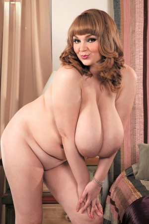 Redhead BBW Micky Bells bares her massive tits before covering her naked pussy