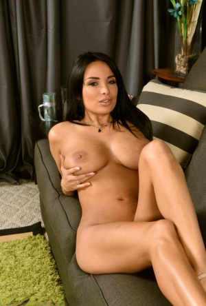 Hot brunette Anissa Kate unveils her hooters as she strips naked on a sofa