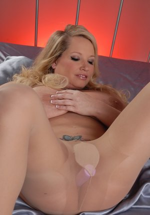 Big titted blonde Rachel Love rips open pantyhose to show her twat on a bed
