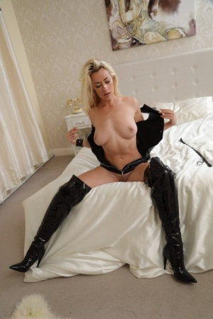 Blond female Rosa sets her firm tits and ass free of a latex bodysuit in boots