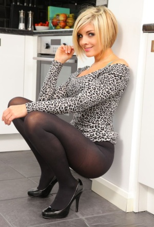 Short haired blonde Naomi K goes topless in a kitchen wearing pantyhose