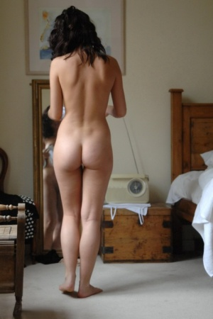 Sexy brunette Bryoni Kate stands naked by a window while trying on new panties