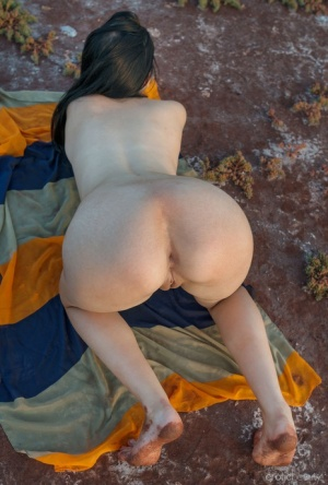 Young brunette Sonny Moor gets naked on a strip of land next to water 90656465