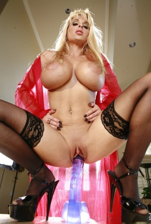 Big titted blond Holly Halston slides a dildo up her snatch in black stockings