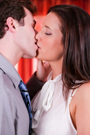 Fully clothed woman Kimberly Kane kisses her man during foreplay action