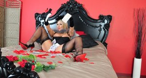 Hot blonde Lucy Zara strokes her pussy with black velvet gloves on her bed