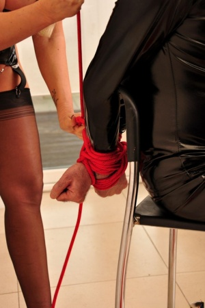 Hot blonde Lucy Zara ties a latex and hood attired man to a chair