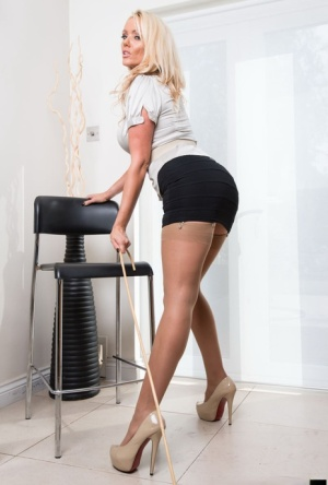 Hot blonde Lucy Zara wields a cane while unleashing her big tits in stockings