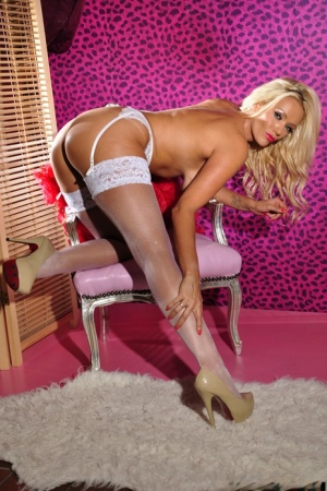 Blonde bombshell Lucy Zara bares her big tits and butt in nylons and garters