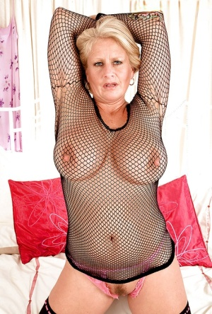 Mature blond in fishnet bodystockings exposing her puffy hooters and twat