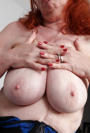 Redhead mature in glasses revealing her flabby curves and exposing her gash