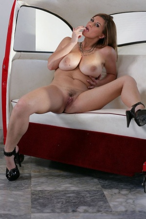 Glamorous temptress revealing her buxom curves and spreading her legs