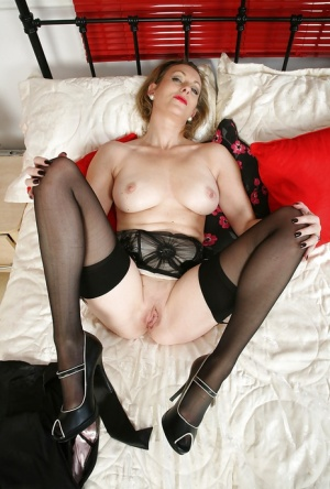 Aged blond broad Betsy Blue poses in bedroom wearing lingerie and stockings