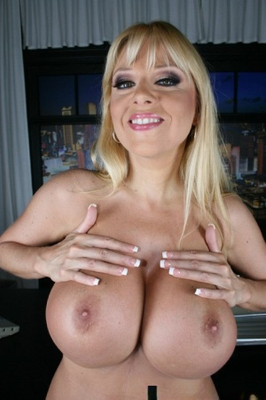 Big titted MILF Harmony Bliss posing in white lingerie in the office