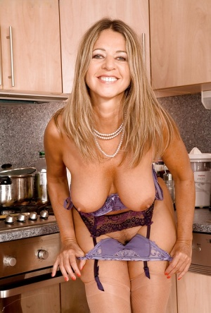 Amateur lady stripping from gartered stockings and sleek lingerie in the kitchen