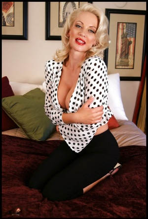 Doll faced blonde babe with big boobs posing solo on the couch