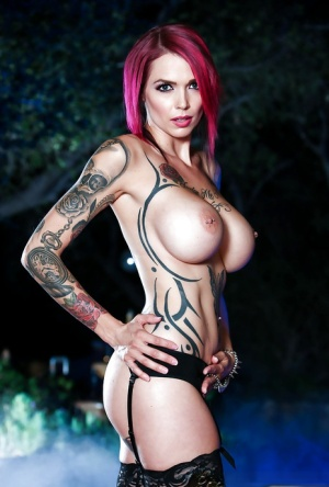 Tattooed redhead babe Monique Alexander exposes large tits and pierced nips