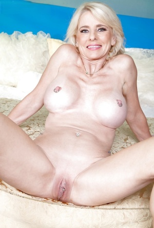 Mature dame Cammille Austin sliding panties aside to expose pierced pussy