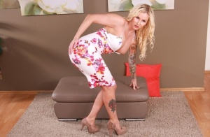 Inked mature blonde Jizella Ross exposing large tits in high heels
