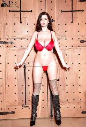 Brunette solo girl Sha Rizel doffing military uniform to pose nude in dungeon