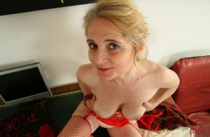 Aged woman Isabella Diana showing off her pussy on desk in red mesh stockings