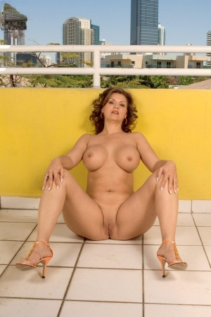 Mature slut Lacey Grant toys her twat lying on the floor on the balcony