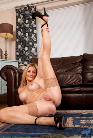 Middle aged blonde dame flashes stocking tops before undressing