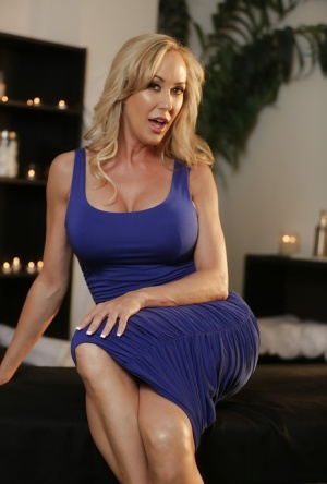 Blonde MILF pornstar Brandi Love baring big tits and nice ass while disrobing