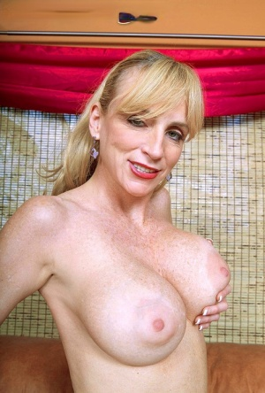 Mature amateur Houston holds her huge boobs while toying her pussy