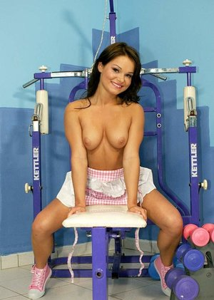 Dark haired female Jeny Baby bares her tits on bench press bench