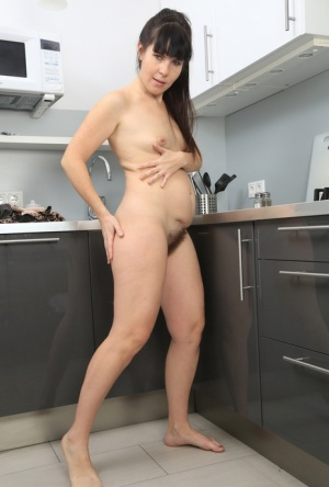 Mature brunette Malavi Mepanse licks her fingers after playing with her beaver 86942175