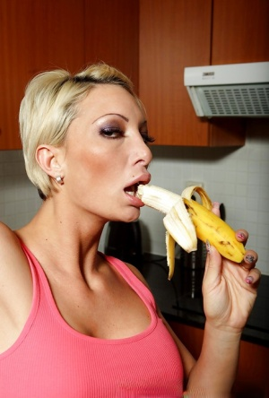 Tight pornstar Pearl Diamond eating a banana and posing naked in a kitchen