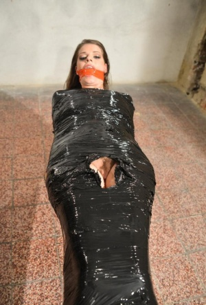 Naked female in high heeled shoes only is mummified in plastic and gagged