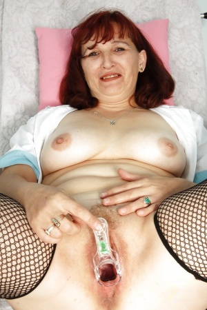 Mature nurse in uniform and fishnet stockings toying her fat cunt