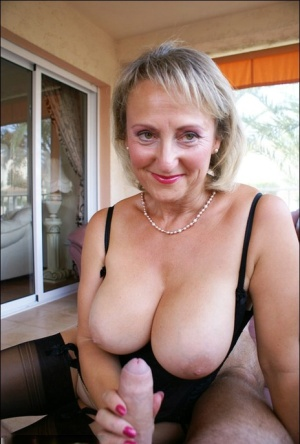 Busty blonde mature fatty teases our imagination by posing in classy black corset