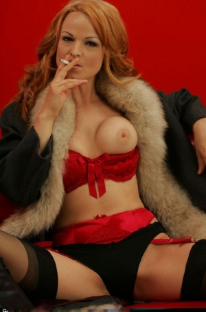 Smoking redhead babe in stockings flashing her boobs and pussy