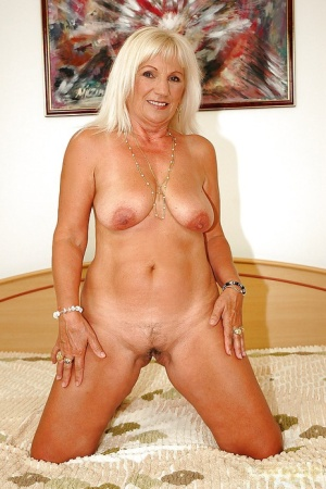 Blonde granny taking off her lingerie and posing naked on the bed