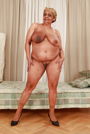 Fatty granny with big flabby boobs stripping off her suit and lingerie