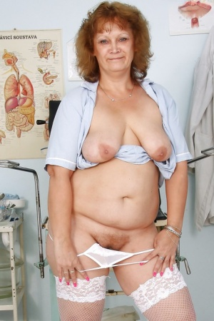 Naughty mature nurse taking off her uniform and exposing her pink twat