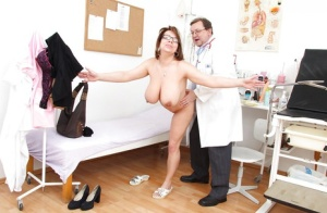 Saucy mature lady with shaved twat and big melons enjoys her gyno exam
